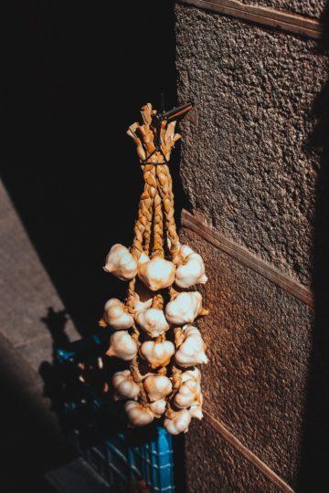 Knoblauchstrang hängt an einer Wand